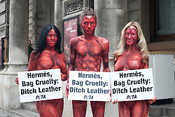 "© licensed to London News Pictures. London, UK 08/05/2012. Three models representing PETA, painted to resemble skinned and bloodied people, holding signs reading ""Hermès, Bag Cruelty: Ditch Leather"" and posing to protest against the leather industry, outside the opening of the ""Hermès Leather Forever"" exhibition at the Royal Academy of Arts today (08/05/12) Model names: (left to right) Maria Harris, Nike Verba, Katy Heffernan Smith. Photo credit: Tolga Akmen/LNP"