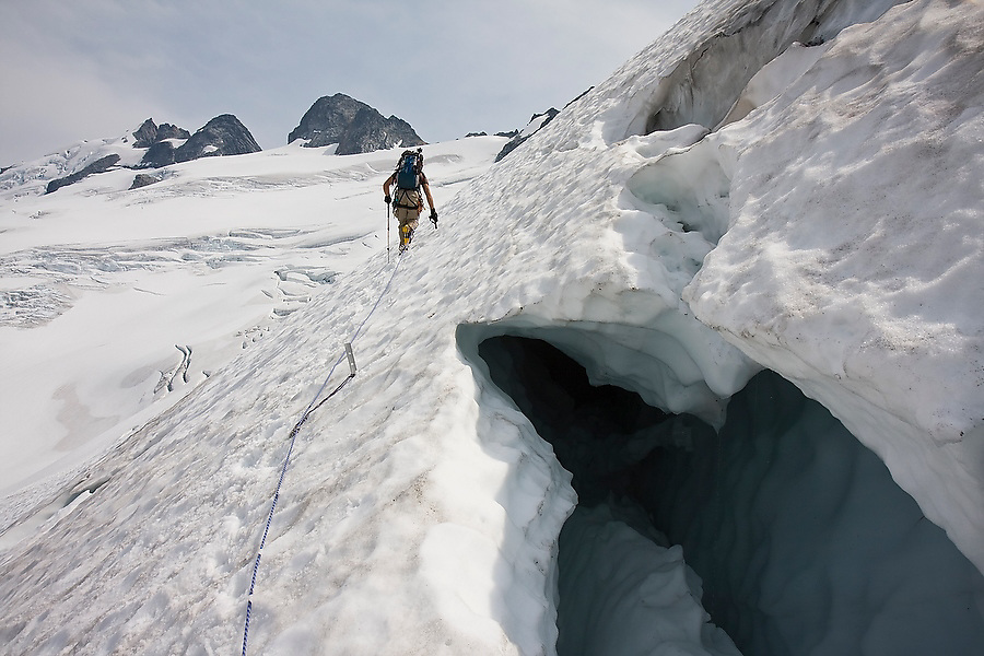 Jim Prager climbs past the crevasses of the Challenger Glacier towards the summit of Mount Challenger, Picket Range, North Cascades National Park, Washington.