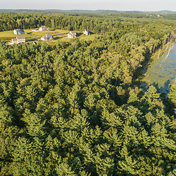 An aerial view of a subdivision near a  beaver pond in a forest in Merrimac, Massachusetts.
