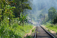 Train tracks lead to the train station (background) in Ella, one of Sri Lanka's most popular tourist destinations. People are standing on the platform, waiting for a train.