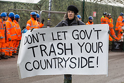 Harefield, UK. 8 February, 2020. A woman carries an anti-HS2 banner during action by environmental activists from Save the Colne Valley, Stop HS2 and Extinction Rebellion to prevent tree felling works for the high-speed rail project. The activists were successful in preventing any of the scheduled tree felling by HS2 and after an intervention by a police officer all tree felling and strimming work has now been cancelled for the weekend.