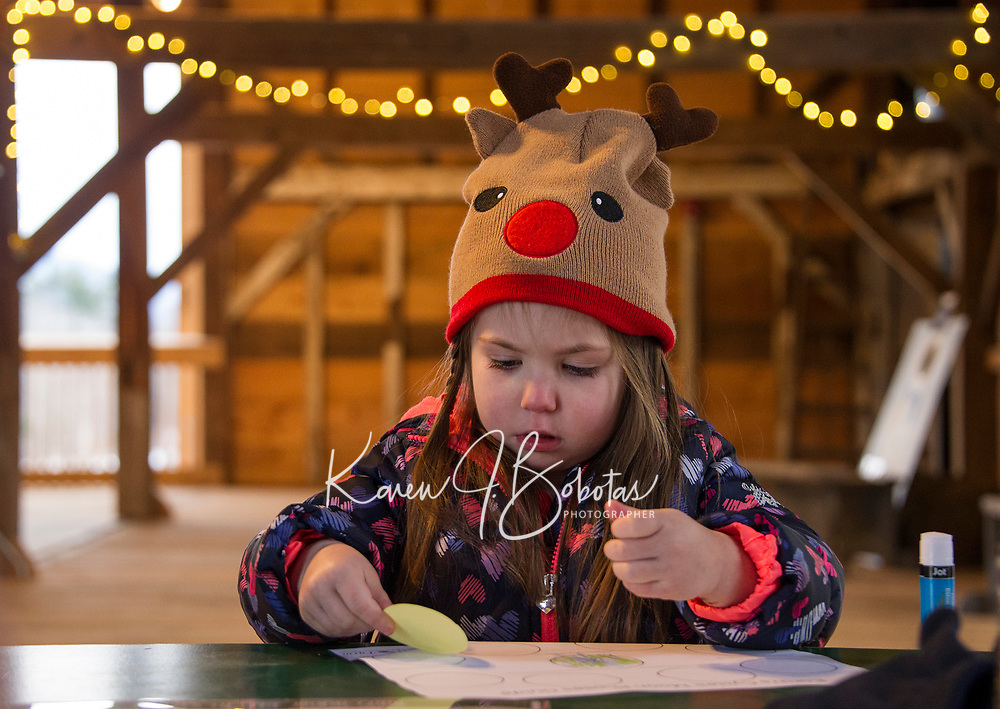 Sophie Dutchka concentrates as she pastes different phases of the moon cycle during a craft activity at Prescott Farm Environmental Center's Winter Solstice celebration Saturday afternoon.  (Karen Bobotas/for the Laconia Daily Sun)