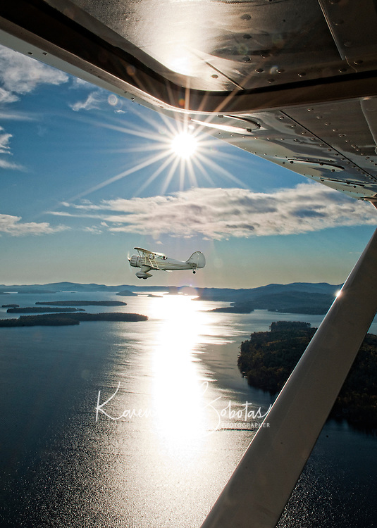 Lakes Biplane taking a scenic fall foliage flight over the Lakes Region of New Hampshire.  Composite image.