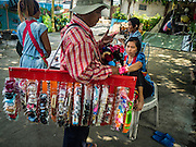 14 OCTOBER 2015 - BANGKOK, THAILAND: A man who sells clothing door to door talks to a resident in the Wat Kalayanamit neighborhood. Fifty-four homes around Wat Kalayanamit, a historic Buddhist temple on the Chao Phraya River in the Thonburi section of Bangkok, are being razed and the residents evicted to make way for new development at the temple. The abbot of the temple said he was evicting the residents, who have lived on the temple grounds for generations, because their homes are unsafe and because he wants to improve the temple grounds. The evictions are a part of a Bangkok trend, especially along the Chao Phraya River and BTS light rail lines. Low income people are being evicted from their long time homes to make way for urban renewal.         PHOTO BY JACK KURTZ