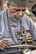 A Nepali man with a hand made musical instrument.