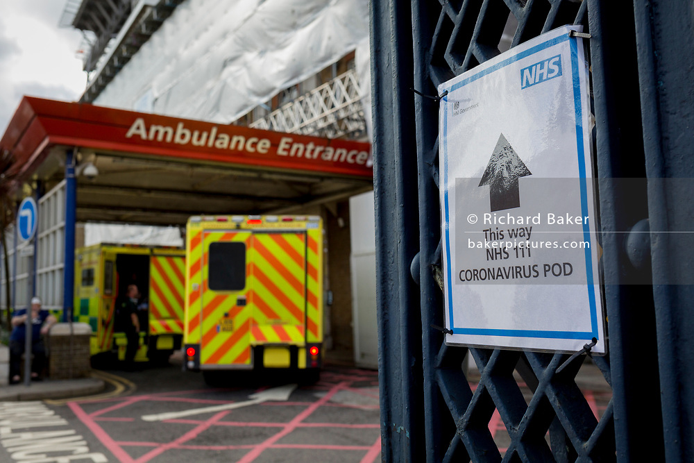 An NHS sign points towards a Coronavirus testing pod, as an ambulance arrives at the A&E Department of Kings College Hospital in Camberwell, south London, on 11th March 2020, in London, England.