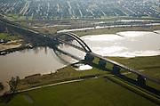 Nederland, Gelderland, Culemborg, 11-02-2008; uiterwaarden van de Lek worden doorsneden door de spoorbrug in de spoorlijn Utrecht - Den Bosch; achter de brug de uiterwaard Goilbedingerwaard en de woonwijk Molenzicht veilig achter de rivierdijk; de aangeslibte klei van de uiterwaard is gedeeltelijk weggegraven om ruimte te maken voor de rivier; pijlers, boogbrug, ..luchtfoto (toeslag); aerial photo (additional fee required); .foto Siebe Swart / photo Siebe Swart