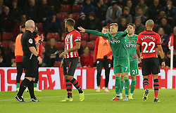 Watford's Gerard Deulofeu reacts after receiving the yellow card from Match referee Simon Hooper (left) during the Premier League match at St Mary's Stadium, Southampton.