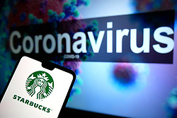 The Starbucks logo seen displayed on a mobile phone with an illustrative model of the Coronavirus displayed on a monitor in the background. Photo credit should read: James Warwick/EMPICS Entertainment