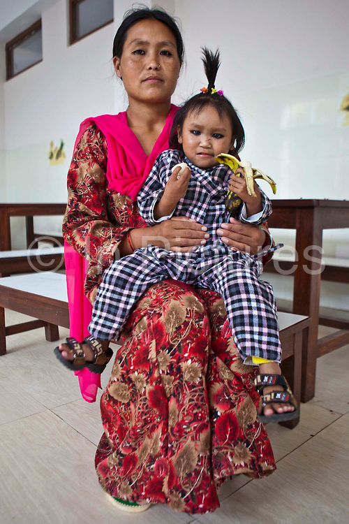 A small, malnourished Nepalese chid sits on her mother's lap holding a banana in the dining room of the Friends of Needy Children Nutritional Rehabilitation Home Kathmandu, Nepal.  She is seven years old, but the size of an average 3 year old due to chronic malnutrition.  She has gained 1.5kg since arriving in the centre 15 days ago.