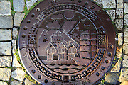 Looking down on old metal manhole cover city of Bergen, Norway