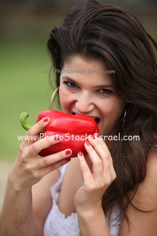 Young woman eats a whole red bell pepper
