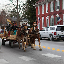 A young Amishman drives horses pulling a farm wagon through the main street of Strasburg, PA.8