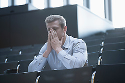 Tensed young man sitting in lecture hall by covering his face, Freiburg im Breisgau, Baden-Wuerttemberg, Germany