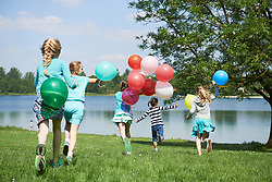 Rear view of girls running in park with balloons, Lake Karlsfeld, Munich, Bavaria, Germany