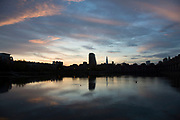 Pink and blue clouds and sky at sunset with a city skyline looking over Shadwell Basin in East London, England, United Kingdom.