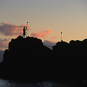 A torch lighting ceremony along Black Rock at sunset in Ka'anapali on the island of Maui.