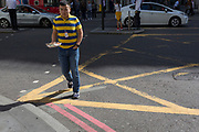 A man wearing a striped top crosses the box juntion on Bishopsgate in the City of London, (aka The Square Mile) the capital's financial district, on 2nd September 2019, in London, England.