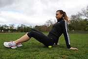A woman exercising in a park in London, UK. Fitness, exercise and wellbeing has never been more popular in the United Kingdom as people strive to live healthy lives. Massaging muscles with a tennis ball.