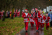 Participants of all ages don Santa suits for the London Santa Dash on Clapham Common. The event was to raise money for the Great Ormond Street Hospital (GOSH) Children's Charity and involved a 5 or 10k run.