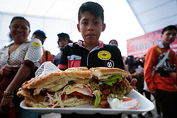 "(170727) -- MEXICO CITY, July 27, 2017 (Xinhua) -- A boy shows a Mexican traditional sandwich named ""Torta"" during the ""Torta Fair"" in Mexico City, capital of Mexico, July 26, 2017. According to local press, during the event which is held from July 26 to 30, people made a ""torta"" of 67 meters long and 820 kilograms in weight, trying to break the world record of the largest torta. (Xinhua/Francisco Canedo) (zy) (Photo by Xinhua/Sipa USA)"