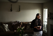 """BIRMINGHAM, AL – FEBRUARY 16, 2018: Anna Lewis, 25, stands in a sober living apartment where she is in recovery for alcohol addiction. <br /> <br /> As a teenager, Lewis first encountered opiates through pain medication that was prescribed to her after a car accident in high school. Oxycontin, the social drug of choice at the time, was so prevalent in her hometown of Pensacola, Fla., that experimentation was easy. """"I didn't even have to look for it. It was just there – at my work, or my friends had it,"""" she said. """"I didn't realize I was addicted until I felt like I had the flu one day, and after using, I felt normal. That's when I knew I had a problem."""" Within a year, Lewis had switched to shooting heroine, and even moved to Atlanta where the drug was cheaper and easier to find. It took an arrest for possession while shoplifting books at a Barnes & Noble to finally realize she was an addict. """"I'd spent all my money on dope,"""" Lewis said. """"So those books were my friends. It's hard to have real friends when you're using. Dope is your priority. The people you're around are sick too, so no one is looking out for you. Everyone's focus is dope."""" At age 19, Lewis finally kicked the heroine habit after checking herself into a detox program, but she soon turned to alcohol. """"It only took about a year for me to become an alcoholic – needing it on a daily basis,"""" she said. Today, Lewis has been sober from alcohol for 3 months, but she says she's painfully aware of the money her mother and grandmother have spent on rehab, and has felt obligated to pay back what she can. """"My mom has always been there for me, and she still is,"""" Lewis said. """"It's been life saving to know that I'm able to call her anytime, and there will be love on the other end of the line."""" <br /> <br /> The addiction crisis that is killing tens of thousands of Americans every year is also creating a financial crisis for many families, compounding the anguish caused by a loved one'�"""