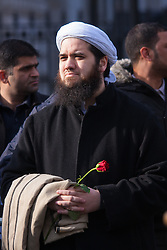 """London, February 8th 2015. Muslims demonstrate outside Downing Street  """"to denounce the uncivilised expressionists reprinting of the cartoon image of the Holy Prophet Muhammad"""". PICTURED: An Iman  holds a rose symbolising love and peace."""