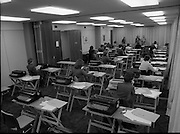 Conference Room at the EEC Building.   (N60)..1981..07.02.1981..02.07.1981..7th February 1981...At the EEC offices, 39 Molesworth Street, the conference room was converted to an examination hall for the purpose of recruiting staff..Image shows the room laid out with secretarial equipment as the applicants take their places for the exam.The Invigilators explain what the applicants are required to do.