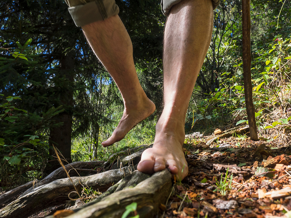 Senior man hiking barefoot in Middle Black Forest Baden-Wuerttemberg, Germany