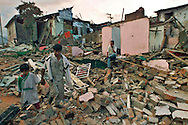 1/26/99 AL DIAZ/MIAMI HERALD--Jose Hernando,6, walks with his father Jose Elize Guaran walks with his father through the rubble of their neighborhood after earthquake in Armenia, Colombia. At right is Jaime Diaz sitting in front of his demolished home.