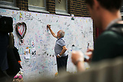 A man writes a message on the ever growing message board of condolences near the tower June 16th 2017, London, United Kingdom. Grenfell Tower burned out after a catastophic fire killing more than 58 people. The tower caught fire early Wednesday morning and final casualty figueres may end up to be many more with police not expecting to be able to find and recover all bodies and to find all missing people. No fire sprinkler in place and cheap cladding made with plastic is so far blamed for the ferocious fire.