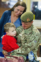 © Licensed to London News Pictures . 25/04/2013. Catterick Barracks , North Yorkshire , UK . Stephen Rumble (Dad , 26) hugs son Stephen Rumble Jnr (2) as Mum Jayne Eaton (23) looks on (from Liverpool) . Soldiers from the 1st Battalion , the Duke of Lancaster's Regiment (1 Lancs) arrive at Catterick Barracks to be greeted by their families this evening (Thursday 25th April), following a six month tour in Lashkar Gah , Helmand Province , Afghanistan . With the UK combat mission due to complete by the end of 2014 , this is likely to be the last deployment by 1 Lancs in Afghanistan , the British Army reports . Photo credit : Joel Goodman/LNP