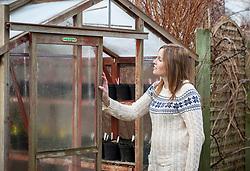 Opening a greenhouse door for ventilation in winter