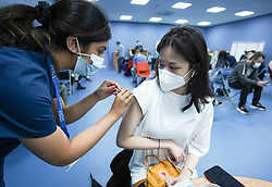 """© Licensed to London News Pictures. 03/07/2021. Sheffield, UK..  Sumyu Lo,23, receives the first dose of the Pfizer/BioNTech vaccine at a pop-up vaccination clinic at Hillsborough Stadium in Sheffield as part of the """"Grab a jab"""" campaign. Photo credit: Ioannis Alexopoulos/LNP"""
