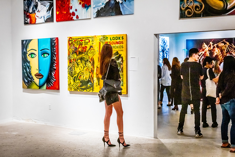 An attractive young woman at Gallery 212 during a monthly Second Saturday Art Walk in Miami's Wynwood neighborhood