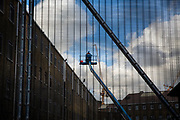 A maintenance worker rises in a cherry picker outside a 4th floor prison wing window at HMP Pentonville, London, UK. HM Prison Pentonville is an English Category B men's prison, operated by Her Majesty's Prison Service. He is working within the exercise yard area which is protected by a large metal fence. (Photo by Andy Aitchison)