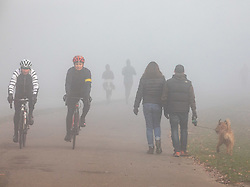 © Licensed to London News Pictures. 27/11/2020. London, UK. Cyclists and walkers enjoy an early morning stroll through the fog in Richmond Park. Walkers, cyclists drivers and Black Friday shoppers were hit with dense fog and a heavy frost this morning as they did the daily commute through Richmond Park, South West London. Yesterday Health Secretary Matt Hancock set out his plans for the end of lockdown on the 2 of December and introduced a new Covid Tier 2 restriction system for London with shops, pubs and restaurants to open up again for the Christmas period. Photo credit: Alex Lentati/LNP