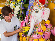 "09 SEPTEMBER 2013 - BANGKOK, THAILAND:  A Thai Hindu places bananas in a statue of Ganesha at the Shiva Temple in Bangkok. Ganesha Chaturthi also known as Vinayaka Chaturthi, is the Hindu festival celebrated on the day of the re-birth of Lord Ganesha, the son of Shiva and Parvati. The festival, also known as Ganeshotsav (""Festival of Ganesha"") is observed in the Hindu calendar month of Bhaadrapada. The date usually falls between 19 August and 20 September. The festival lasts for 10 days, ending on Anant Chaturdashi. Ganesha is a widely worshipped Hindu deity and is revered by many Thai Buddhists. Ganesha is widely revered as the remover of obstacles, the patron of arts and sciences and the deva of intellect and wisdom.    PHOTO BY JACK KURTZ"