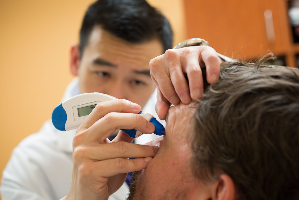 Dr. Steven Yeh (left), an ophthalmologist, performs an eye exam on Dr. Ian Crozier at the Emory Eye Center on Friday, March 27, 2015 in Atlanta, Ga. Crozier survived Ebola and now suffers from some strange side effects because of the disease. Here, Yeh is testing the pressure of Crozier's eyes. Kevin Liles for The New York Times