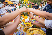06 JANUARY 2013 - BANGKOK, THAILAND:  People reach for flower garlands recently blessed by monks after a service for a relic that is a piece of the Buddha's hair. The relic has been on display in Bangkok for about 10 years. There was a ceremony in Sanam Luang in Bangkok Sunday to honor the relic. People prayed for it and received blessings from Buddhist monks and Brahmin priests who presided over the service. The hair is being moved to Ayutthaya, where it will be displayed in a Buddhist temple. The piece of hair has been on loan to Thai Buddhists from a Buddhist temple in Sri Lanka.   PHOTO BY JACK KURTZ