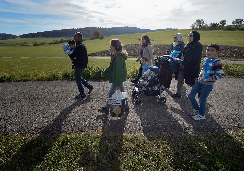 Syrian refugees walk through the countryside outside Messstetten, Germany. They have applied for asylum in Germany and are awaiting word on the government's decision. Meanwhile, they live in a room in a former army barracks in Messstetten.