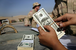 Alyaa Abdul Hassan Abbood, a translator, counts money at the base of the 82nd Airborne to give to Iraqi civilians for  damages caused by U.S. troops in Baghdad, Iraq, Sept. 27, 2003.