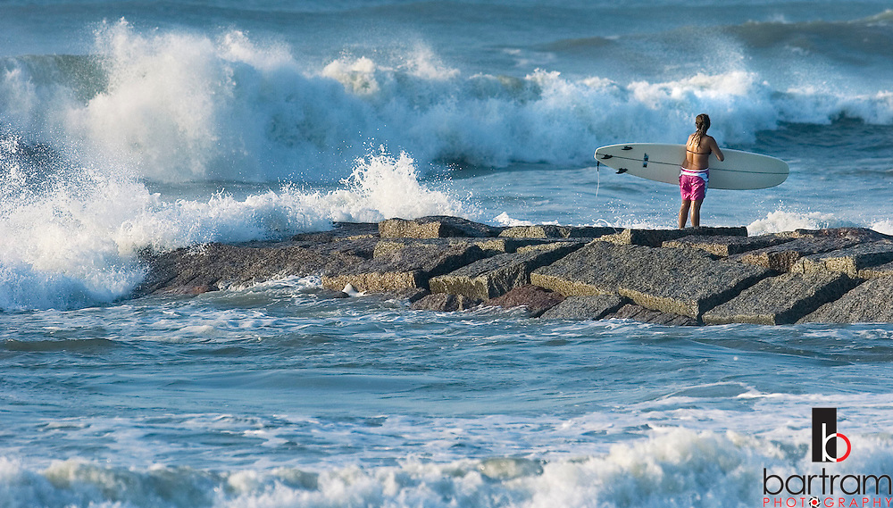 KEVIN BARTRAM/The Daily News.A surfer stands on the rocks near 39th Street and Seawall Boulevard before jumping into the waves generated by Hurricane Katrina on Monday, August 29, 2005. Hurricane Katrina made landfall near New Orleans on Monday.