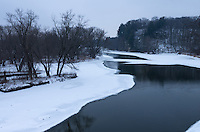The Rock River flows quietly between small islands and steep bluffs. The side of the river was covered with ice but the middle remained ice free.<br />