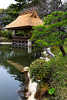 Seifukan Teahouse at Shukkeien Garden - Shukkeien garden was built in 1620 by Ueda Soko - a warrior who became a Buddhist monk, tea master and landscape gardener.  It was designed and built for the villa of Asano Nagaakira, daimyo of Hiroshima.  Shukkeien distorts concepts of space, cramming a miniaturized version of the landscape of West Lake Hangzhou China into a space of just 40,000 square meters.  Even its name means shrunken-scenery garden. Shukkeien contains many of the elements of classic landscape gardens introduced from China by Zen priest Muso Kokushi: evocatively shaped rocks, pavilions and a large pond with small islands. Around Takuei Pond with its hump-backed Rainbow Bridge winding paths lead visitors through miniature mountains, valleys, fields and groves.  Shukkeien's Seifukan teahouse, with its thatched roof and lyre-shaped window, a different tea ceremony is held each month to celebrate the flowers of each successive season.