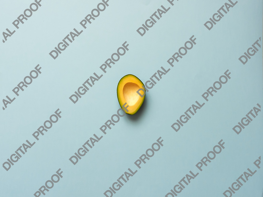 Avocado without seed isolated in blue background viewed from above - flatlay look