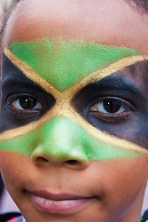 """London, August 24th 2014. A boy, his face painted in the colours of the Jamaican flag, gazes into the camera as thousands of Londoners of all races and cultures attend Notting Hill Carnival's """"Family friendly"""" day ahead of the main carnival on August Bank Holiday Monday."""