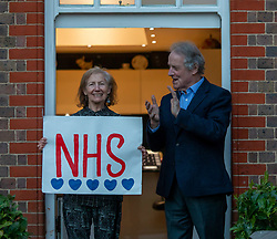 © Licensed to London News Pictures. 09/04/2020. London, UK. Recovering cancer patient Paul Morgan 76 and his wife Carolyn 84 from Wandsworth who have been self-isolating for 4 weeks clap for the NHS as millions of Brits around the country applaud the NHS and frontline workers this evening as Prime Minister Boris Johnson leaves ICU department at St Thomas's Hospital. Photo credit: Alex Lentati/LNP