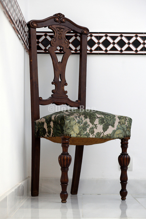 a wooden old classic chair indoors on a white marble floor