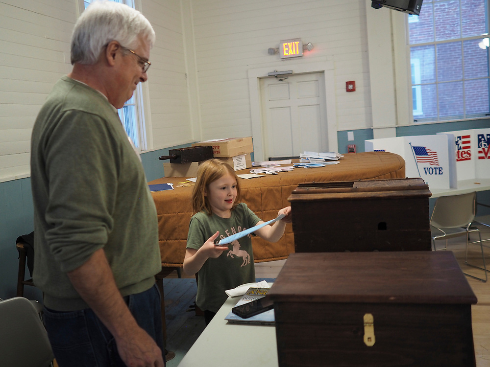 A young girl in Nelson, New Hampshire places a ballot into a wooden ballot box that is more than 100 years old.